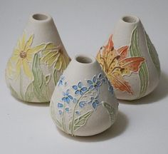 Botanical trio of bud vases in bisque ware form. Hand painted with morning glory blue, willow yellow, coral red, chartreuse, ivy green, and mahogany underglazes. Clear glaze was then applied on top.