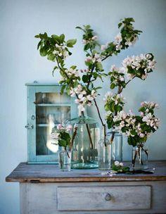 Mooie bloesemtakken. Soortgelijke brocante tafeltjes, kleine wandkastjes en glazen flessen zijn ook te vinden op www.grijsengroen.nl