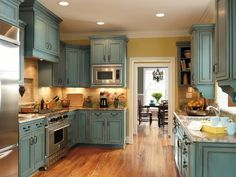 Blue cabinets complement warm gold walls & wood flooring