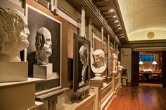 View of the cast hall looking toward the front library. Highly finished charcoal drawings are copied from plaster casts displayed on built-in pedestals which are connected to storage cabinets below. Note the ceiling compartments have been lightly sketched onto the scratch coat of plaster to indicate the compositional design for the eventual fresco.