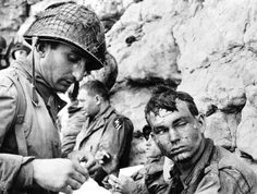 Wounded U.S. soldiers are treated for burns at a secure location on a Normandy beach.