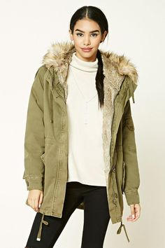 A heavyweight woven parka featuring a buttoned and zippered front, detachable faux fur lining, detachable hood, drawstring waist, buttoned epaulets, two front flap buttoned pockets, on-sleeve flap pocket, and long button cuff sleeves.