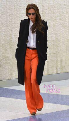 Victoria Beckham owns it in orange at JFK airport