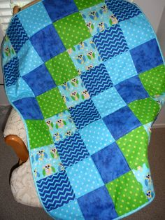 Here is a beautiful cuddle flannel handmade baby or toddler quilt bright and colorful with carton owls on light blue, blue chevrons, polk a dots in blue and polk a dots in green, and a blue marble ble