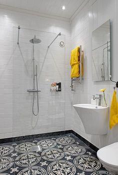 Na podłodze płytki z marokańskim wzorem, prysznic bez brodzika, biel i.. żółte dodatki. Ciekawa armatura i dodatki (np wieszak na ręczniki) , i rozwiązanie z jedną szklana taflą oddzielającą prysznic od reszty pomieszczenia.  via: alvhemmakleri