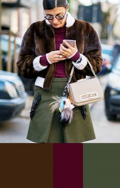 Giovanna Battaglia wears a burgundy sweater, chocolate brown fur bomber jacket, army green embellished miniskirt, and a neutral bag