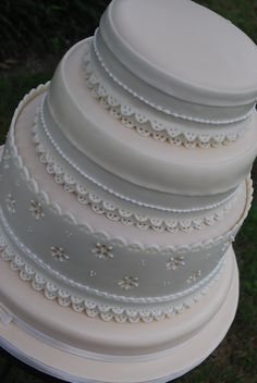 """Eyelet Lace wedding cake - This cake was covered in an ivory colored fondant.  We then added white fondant bands.  Royal icing was also used for some smaller details.  The complete secret to a cake like this is to use Fondarific for the """"white"""" part on this cake.  You have to poke all the holes in the bands while on the work table, chill them so they don't lose their shape and then apply to the cake,  Better when two people deal with the bands applications.  It took a long time to cut all of…"""