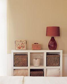 red lamp, tan walls, white bookshelf,  wicker baskets...Master Bedroom