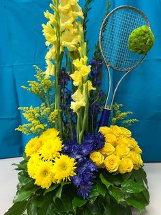 Tennis racket with a floral ball. Yellow and blue arrangement. Designed by CS Events and Floral, Las Vegas, Nevada.