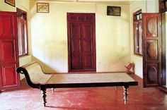 A caned daybed from Kerala placed between two open doorways provides a breezy resting spot. I want one...