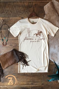 "- ""Poncho & Lefty livin on the road"" graphic t-shirt - Brown graphics on oatmeal - Desert and cowboy scene graphics - Junior size t-shirt, long thru bodice - Slim fitting t-shirt, small fits size 0-3,"