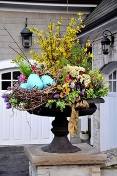 Easter flower urn with forsythia, large nest of eggs and spring flower idea for front door.