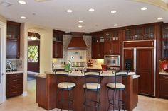 Traditional Kitchen with Custom hood, Kitchen island, Raised panel, Simple granite counters, Stone Tile, L-shaped, Flush