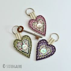 Handmade heart shaped fabric key rings decorated with applique, freehand machine embroidery and a mother of pearl button www.stitchgalore.com