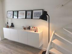 Hangend meubel (Ikea) en staande fotolijsten op plank. Lamp serie hektar van Ikea.