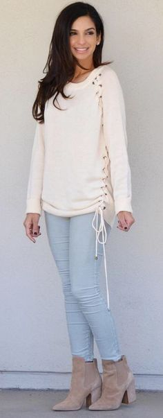 Ivory lace up sweater. Pair with jeans or leggings your favorite pair of boots. Also available in heather gray and black. Knit sweater with lace up accent and scoop neck. Cotton/acrylic/nylon blend.