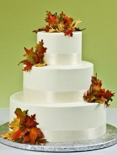 Simple white three tier autumn leaves wedding cake. The leaves are yellow, orange, brown, tan and green. Decorated with satin white ribbon around each tier. From www.jacquespastries.com #wedding #cake #birthday