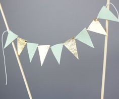 A cake banner made from felt flags in mint and metallic gold. 9 mini felt flags are sewn on white string to make this wedding cake topper. Not