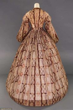 """PAISLEY PRINTED PURPLE DRESS, MID 1860s Purple sheer cotton organdy w/ paisley patterned vertical rows, CF bodice opening w/ ribbon trim, balloon sleeves & small cuffs, gathered full skirt, B 33"""", W 27"""", L 59"""", (scattered tiny & small holes, underarms stained, repairs to shoulder & skirt back, hem edge dirty) fair."""