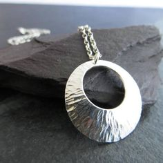This sterling silver pendant has been hand formed using traditional methods: I cut the silver disc, smoothed and then textured it with an elongated dimple pattern. This textured silver pendant was then given a domed shape before being attached to the sterling silver belcher chain. It