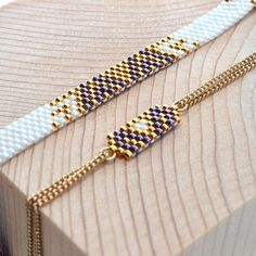 ALIA et ALPHA en violet, blanc et or. chaîne et fermoir en plaqué or.