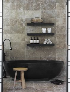Black tub and shelves, beige marble tile in this luxe bathroom. Even the bathroom toiletries look beautiful Black Bathtub, Black Tub, Modern Bathtub, Bathroom Black, Bathtub Dream, Black Marble, Warm Bathroom, Stone Bathtub, Concrete Bathroom