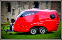 The stunning 21st century TripBuddy camping trailer juxtaposed in front of the ruins of an ancient  medieval castle in Tutbury, England.