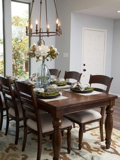 The Gaspar dining room is illuminated by a new chandelier and a glass vase with bright white flowers serves as the centerpiece of the dining table, as seen on HGTV's Fixer Upper.