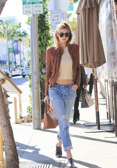 Gigi Hadid wears a brown leather jacket with a camel sweater, cuffed boyfriend jeans and black loafers.