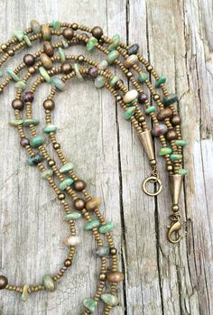 Hand strung necklace made from green turquoise chips, Czech glass seed beads, rainforest jasper and antiqued brass. The strands come together with antiqued brass cones. 17 in length.