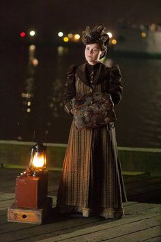 Lizzie in episode 206. Brown silk strip and matching velvetine coat with brown feathered hat and muff. All made in our workroom.