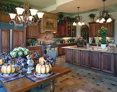 Tuscan style kitchen design - oak cabinets in combination with stone counters, backsplashes and floor. There is also a beautiful oak table, chandeliers and a lot of green