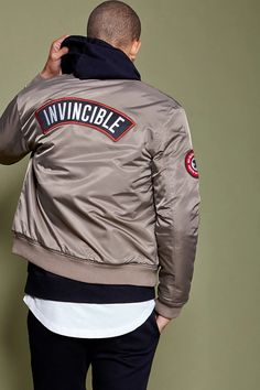 "A woven padded bomber jacket with long sleeves, ribbed knit trim, a zippered front, a zippered sleeve pocket, snap-buttoned flap pockets on the front, an interior chest pocket, a sleeve patch with an embroidered ""No Guts No Glory"", ""99"" with stars embroidered on the chest, and a back ""Invincible"" patch."