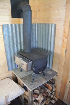 I am looking to install this kind of corrigated metal behind my new wood stove.found on Colorado Cylinder Stoves: A Great Woodstove for a Tiny House Tiny House Cabin, Tiny House Living, Tiny House Design, Ice Shanty, Tiny Wood Stove, Small Stove, Fishing Shack, Ice Fishing House, Wood Burner
