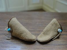 Teresa Dudley - pair of tan suede moccasins with a silver and turquoise button at the side, made in 1988; sold on ebay for $9.39