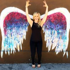 Kendall, owner of The Bar Method Santa Barbara, looks like she's ready to fly as she shows off her balance while doing heel lifts in front of angel wings in Los Angeles! #WhereDoYouBar?