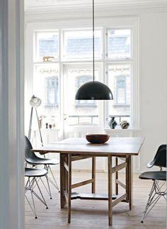Lotte har mikset de enkle, sorte Eames-stole med et rustikt spiseklapbord fra Sverige. Pendlen i industristil er fra Ikea.
