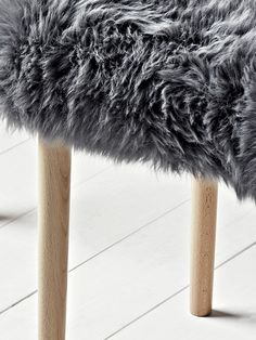 Carefully handmade in the UK, our sheepskin dressing table stool seat cover is crafted from natural long haired sheepskin in a muted slate grey colour. Rectangular in shape, with four slim, tapered birch wood legs, this sumptuous stool has an uphol