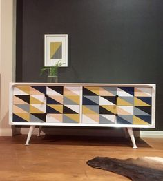 'Number 38' 1950s four drawer lowboy console by Kerby Furniture of Melbourne. Casing and splayed legs in gloss white enamel. Oblong Tri Geometric pattern to drawer fronts hand painted and sealed. Drawers slide perfectly and are dressed with new black metal barrel knobs.