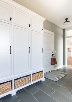 Blue and gray mudroom. Blue slate tile, white lockers and baskets in this lake house mudroom.