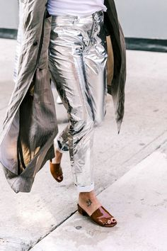 When it comes to metallic pieces we tend to gravitate towards the safer options like bags and shoes. The shiny accessories and pair of sandals, flats, or boots allow us to add some shiny flair without it overwhelming our look. It wasn't until we came across this street style shot from New York Fashion Week earlier this month, that we started considering taking our love for metallics to the next level with a cool pair of silver statement jeans.