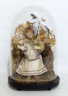 Enfant Jésus en cire sous son globe, dans un décor de papier rocher, fleurs séchées, et fleurs en tissus. Epoque Napoléon III. Haut. Totale : 44 cm.