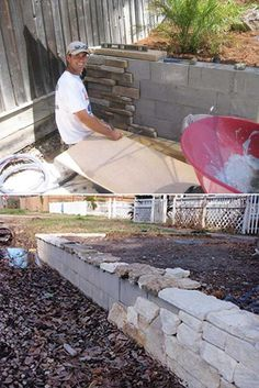 Build a backyard retaining wall with concrete blocks and then adorn it with stone facade. Nice!