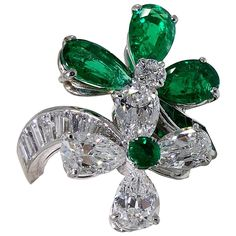 Fine emerald and diamond platinum ring set with approximately 3.0 carats of emeralds and 4.50 carats of diamonds. The crossover flower design is very similar to the 'Clover' design by VCA. Circa 1990.