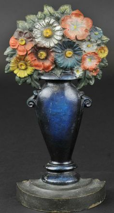 "MIXED FLOWERS IN VASE DOORSTOP Marked B&H, beautifully detailed colored flowers, deep blue sleek tall vase on half round heavy base, rubber knobs intact. 11 1/2"" h. (Near Mint Cond.)"