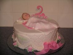 "Baby Doll Cake - I used 8"" doll for the baby, placing her on a pink fondant blanket and covered her w/white fondant blankie w/stenciled pink design. Fondant bow, name plaque, 2 and pillow.  Diamond imprint on BC w/BC ruffles and roses.  Sour cream vanilla w/strawberry filling."
