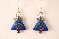 These lovely blue dangle earrings are a spin off from my Fantasia series, with sterling wire work and ear wires. I found some beautiful faceted amethyst beads for the touch at the bottom. They have a decorative impressed floral pattern on the back and drop about 1 from the bottom of the ear wire. These are so light weight you hardly know your wearing them