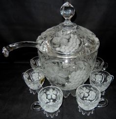"""CUT CRYSTAL PUNCH SET, NINE PIECES:Includes one punch bowl with lid, H 13"""", grape designs; one ladle; and six cups, H 3""""."""