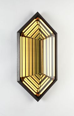Rosie Li  STELLA HEXAGON  Inspired by his early work, this sconce collection is named after American painter Frank Stella. When illuminated, its half-mirrored glass diffuser reveals a series of nested geometric shapes. Stella creates the impression of infinite volume within a