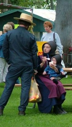 A young Amish mother feeds her baby, as she talks to her husband.....